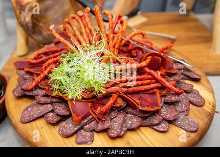 Food tray with delicious salami Meat platter with selection - Cutting sausage and cured meat on a celebratory table - Stock Photo