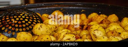 Preparation of small potatoes to butter potatoes with rosemary in the pan, spatula on the edge - Stock Photo