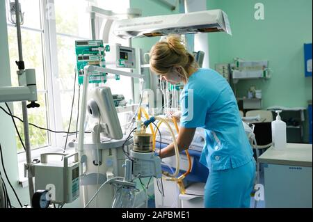 At the intensive care unit. Nurse standing near hospital bed with baby preparing it for treatment. Childrens Cardiac Center.May 18,2018. Kiev, Ukraine