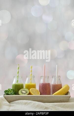 four colorful fruit smoothies in a row with fresh fruits in front of neutral light blur bokeh background with copy space above for a healthy lifestyl - Stock Photo