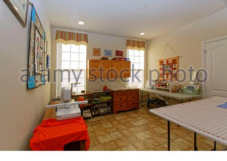 sewing room, house, bright light, 2 windows, fiber art wall decorations, cabinets, cutting table, sewing machine, work table, supplies, horizontal; PR - Stock Photo