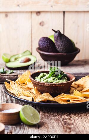 Mexican traditional food, guacamole sauce, ingredients  avocado, cilantro, lime and tortilla corn chips on wooden rural table. Preparing local food