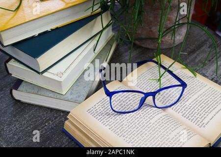 VIERSEN, GERMANY - AUGUST 21. 2019: View on open yellowed book with blue reading glasses and stack of old books on round wood table. Succulent plant b - Stock Photo