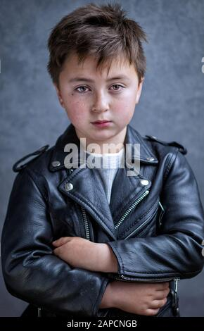 Handsome multi-racial Asian Caucasian little juvenile delinquent boy wearing a black leather motorcycle jacket with arms crossed in a defiant pose wit - Stock Photo