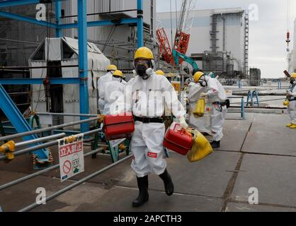Okuma, Fukushima, Japan. 22nd Jan, 2020. Fully-protected workers leave Unit 2 reactor house after their work at tsunami-devastated Tokyo Electric Power Company (TEPCO) Fukushima Daiichi Nuclear Power Plant in Okuma town, Fukushima Prefecture, 22 January 2020. The storage tanks including water processed in the ALPS will be full around summer of 2022, TEPCO has told. Japanese government need to decide soon how manage the processed water still including tritium. Credit: Kimimasa Mayama/POOL/ZUMA Wire/Alamy Live News - Stock Photo