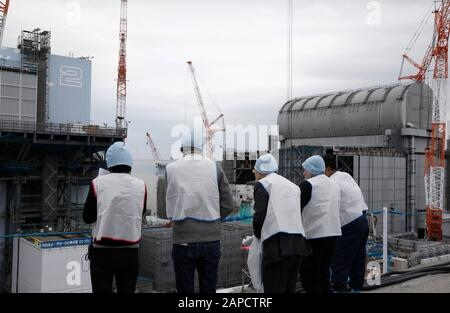 January 22, 2020, Okuma, Fukushima, Japan: Journalists inspect Unit 2 (L) and Unit 3 (R) reactor houses during their inspection tour at tsunami-devastated Tokyo Electric Power Company (TEPCO) Fukushima Daiichi Nuclear Power Plant in Okuma town, Fukushima Prefecture, 22 January 2020. The storage tanks including water processed in the ALPS will be full around summer of 2022, TEPCO has told. Japanese government need to decide soon how manage the processed water still including tritium.  (Credit Image: © Kimimasa Mayama/POOL via ZUMA Wire) - Stock Photo