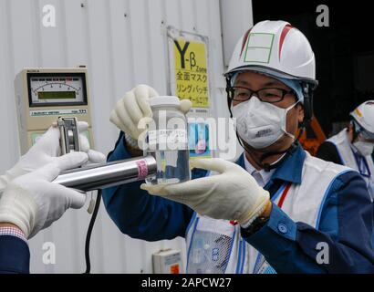 Okuma, Fukushima, Japan. 22nd Jan, 2020. Workers of Tokyo Electric Power Company (TEPCO) Fukushima Daiichi Nuclear Power Plant demonstrate to measure radiation of water processed in ALPS (Multi-nuclide retrieval equipment) II in front of the ALPS II building at the tsunami-devastated nuclear power plant in Okuma town, Fukushima. Japanese government will need to decide soon how manage the processed water still including tritium. Credit: Kimimasa Mayama/POOL/ZUMA Wire/Alamy Live News - Stock Photo