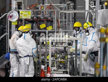 Okuma, Fukushima, Japan. 22nd Jan, 2020. Fully covered workers check water processing system ALPS(Multi-nuclide retrieval equipment) where process contaminated water to store in tanks at ALPS' house of tsunami-devastated Tokyo Electric Power Company (TEPCO) Fukushima Daiichi Nuclear Power Plant in Okuma town, Fukushima Prefecture, 22 January 2020 after transferring to new tanks. The storage tanks including water processed in the ALPS will be full around summer of 2022, TEPCO has told. Japanese government will need to decide soon how manage the processed water still including tritium. (Cred - Stock Photo