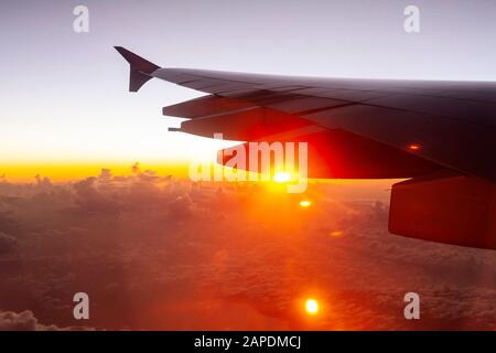 The sun peeks out from beneath the wing of an airplane on a long-haul international flight.  A cloudscape of fluffy cumulus clouds is far below. - Stock Photo