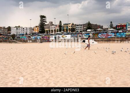 A surfer carries his surfboard across famous Bondi Beach on a cloudy day in mid-summer. - Stock Photo