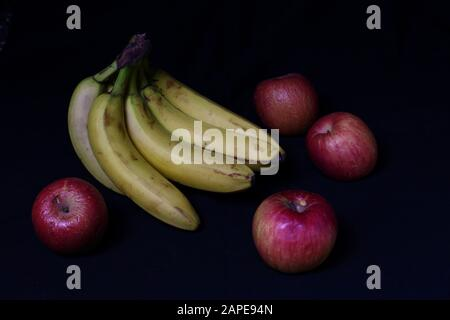 A high angle shot of delicious bananas and apples on a black surface - Stock Photo