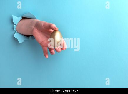 Golden egg in a female hand on a blue background with a hole. Horizontal orientation with copy space.
