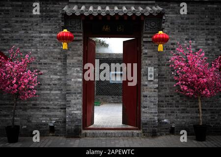 Red door and gate giving entrance to a private courtyard and a dwelling house in a hutong alley in Beijing, China. Decorated for the Chinese New Year - Stock Photo