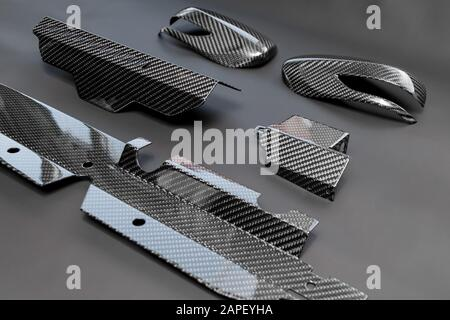A close-up on a car exterior elements made from carbon fiber of interwoven black and gray color from heavy-duty yarns for the production of light and - Stock Photo