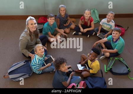 Female school teacher sitting cross legged on the floor in a circle with a group of schoolchildren i - Stock Photo