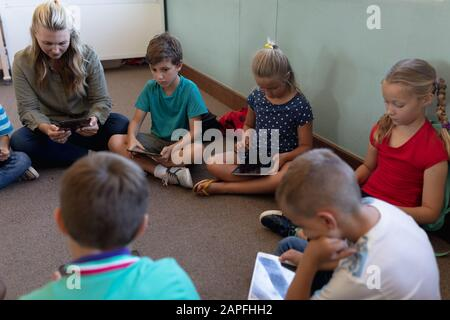 Female school teacher sitting cross legged on the floor in a circle with a group of schoolchildren a - Stock Photo