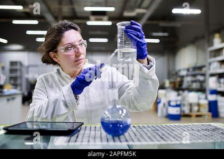 Young lab assistant with flask and tablet in hands on blurred background - Stock Photo