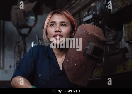 Diverse female industrial engineer holding welding helmet after work shift - Young Asian factory metal worker taking a break - Hispanic apprentice woman, learning new skills on internship training - Stock Photo