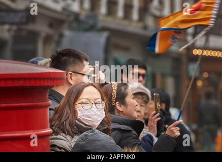 Anti-coronavirus face mask worn by a chinese tourist outside Trinity college, university of Cambridge, England, UK, threaton 22nd February 2020. - Stock Photo