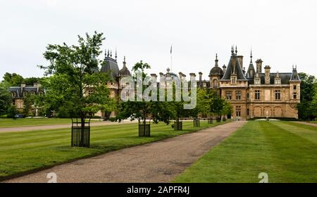 Dramatic approach view of Waddesdon Manor, former home of Ferdinand Rothschild. Immaculate front lawn and tree-lined entrance paths. No people. UK.