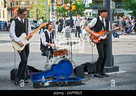 Vancouver, B.C., Canada: Three student Beatles revival musicians performing openly in downtown area to improve their budget - Stock Photo
