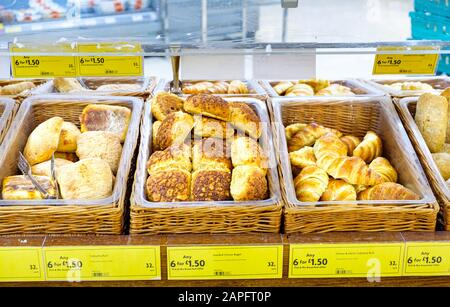 Wide selection of freshly baked various bread rolles, and croissants pick and mix offers displayed in wicker bread baskets at the bakery department. - Stock Photo