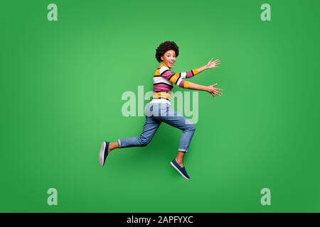 Full size profile side photo of funky crazy afro american girl jump run speedy want hug embrace her best fellow wear bright shine clothing isolated - Stock Photo