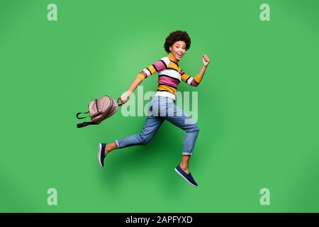 Full size profile side photo of funky crazy afro american girl jump hold bag run after fall black friday discount wear bright shine clothes isolated - Stock Photo