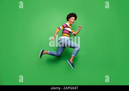 Full size profile side photo of positive cheerful afro american girl jump run after fall black friday bargain wear denim jeans outfit isolated over - Stock Photo