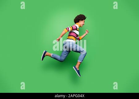 Full size profile side photo of funky afro american girl jump run after incredible black friday fall discounts wear stylish clothing isolated over - Stock Photo