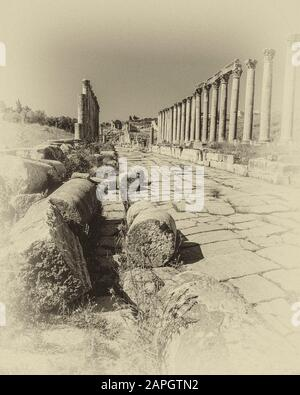 Jordan. Free standing stone colonnades in monochrome on the once main street of the ancient Roman City of Jerash not far from the Jordan capital city of Amman in the Middle East - Stock Photo