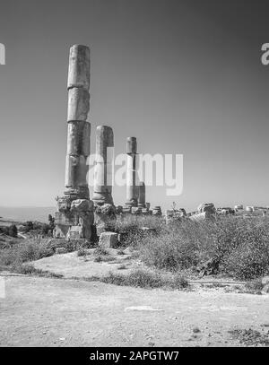 Jordan. Free standing stone columns in monochrome is all that remains of the ancient Roman City of Jerash not far from the Jordan capital city of Amman in the Middle East - Stock Photo