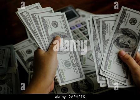 Businessmen women counting money on a stack of 100 US dollars banknotes - Stock Photo