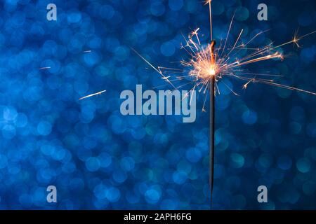 Party sparkler burining over blue bokeh background - Stock Photo