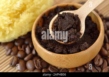 Homemade coffee scrub face mask in wooden bowl with spoon on coffee beans - Stock Photo