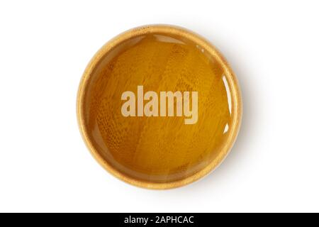 Oil in wooden bowl on white background - Stock Photo