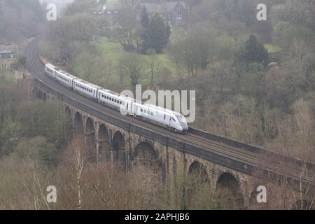 An unbranded TransPennie Express train crosses the viaduct at Brownhill, Saddleworth, Oldham heading for Manchester. - Stock Photo