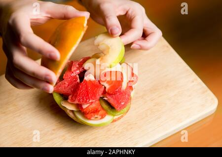 girl puts a slice of apple in a grapefruit burger in which sliced fruits and berries lie, top view - Stock Photo