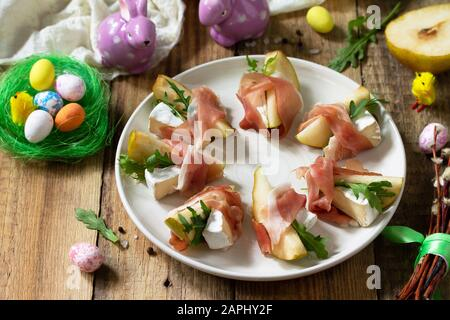 Festive snacks. Pear appetizer with jamon, arugula and brie cheese on a rustic wooden table. - Stock Photo
