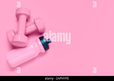 Fitness workout background concept with pink dumbbells and bottle of water. Top view flatlay sport, diet and healthy lifestyle with training equipment - Stock Photo