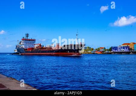 Willemstad, Curacao, Netherlands - December 5, 2019: Cargo tanker ship entering Willemstad , Konigin Juliana Bridge in the background Curacao - Stock Photo