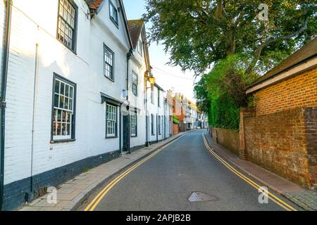 Shady narrow street with white and black buildings on one side and red brick wall on other side and yellow  lines leading through town. - Stock Photo