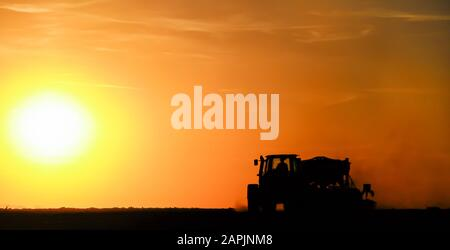 Silhouette of a tractor sowing seeds in a field in a cloud of dust against the background of the setting sun. - Stock Photo