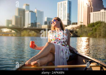 Beautiful woman relaxing on a boat, summer day on lake with city skyscrapers in background, commercial travel concept - Stock Photo