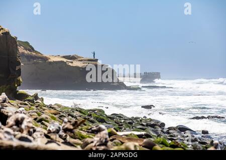Person on a cliff, taking a selfie with people in the far background and rocks in the foreground. Sunny Day on the California Coast - Stock Photo