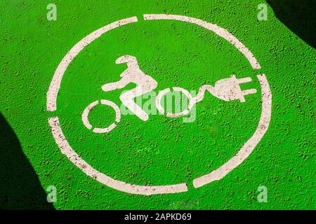 Electric motorcycle parking with charging station sign painted on asphalt. White symbol of a motorcycle with socket plug on green background. - Stock Photo
