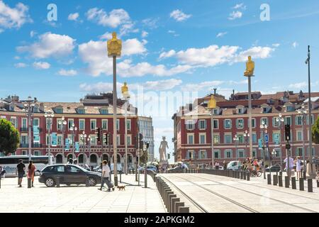 The seven statues art display representing the continents rise about Place Massena as tourists walk by on a summer day on the French Riviera. - Stock Photo