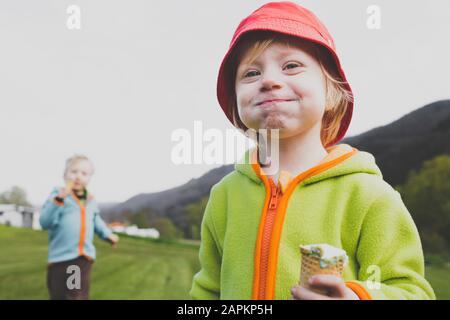 Portrait of little girl eating ice cream outdoors - Stock Photo