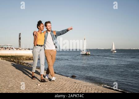 Happy young couple walking on pier at the waterfront, Lisbon, Portugal