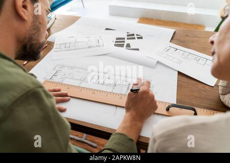 Crop view of two architects working together at desk in office - Stock Photo